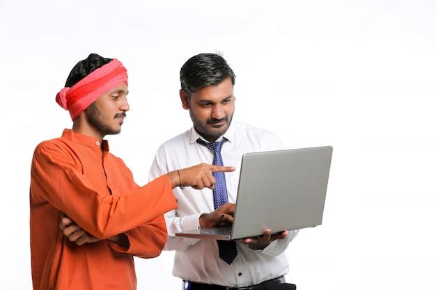 Agent de banque indien ou employé du gouvernement d'entreprise montrant des informations à l'agriculteur dans un ordinateur portable.