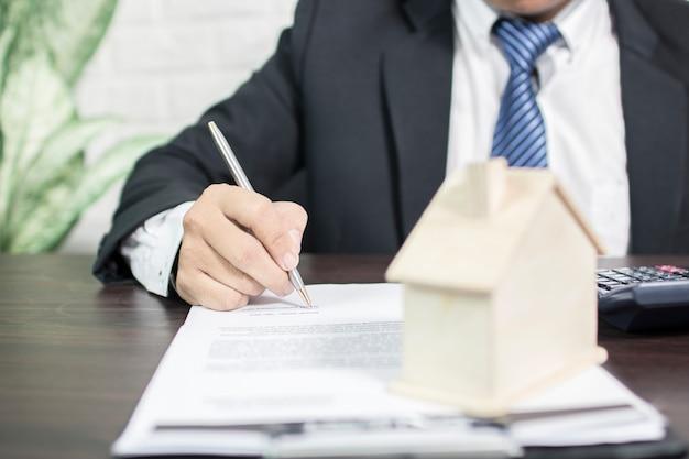 Un agent de la banque signe un contrat pour approuver le financement de la maison.