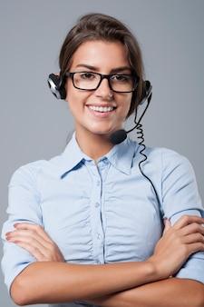 Agent de centre d'appels féminin posant avec un casque avec micro
