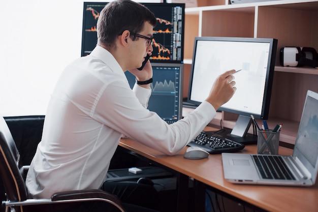 Un agent de change en chemise travaille dans une salle de surveillance avec des écrans d'affichage. graphique de la bourse forex trading finance. hommes d'affaires négociant des actions en ligne