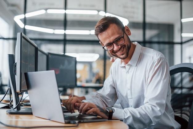 Un agent de change masculin en vêtements formels travaille au bureau avec le marché financier.