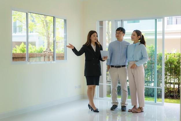 Agent de courtage immobilier femme asiatique montrant un détail de la maison dans sa tablette numérique