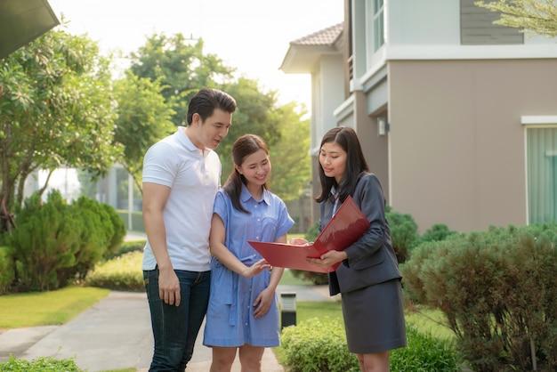Agent de courtier immobilier femme asiatique montrant un détail de la maison dans son dossier au jeune couple amoureux asiatique à la recherche et l'intérêt de l'acheter.