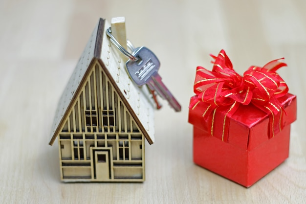 Agent de courtier immobilier avec modèle de maison, boîte-cadeau et clés