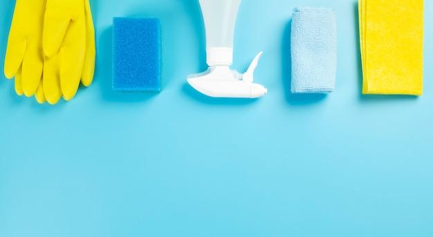 Agent de détergents et de produits de nettoyage, éponges, serviettes et gants en caoutchouc, fond bleu. vue de dessus. copier l'espace