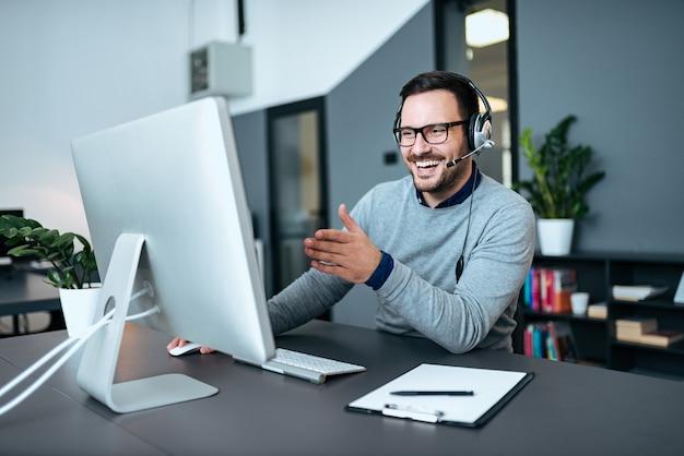 Agent du centre d'appel souriant parlant au téléphone et regardant un moniteur.