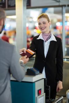 Agent d'enregistrement de la compagnie aérienne remettant le passeport au navetteur