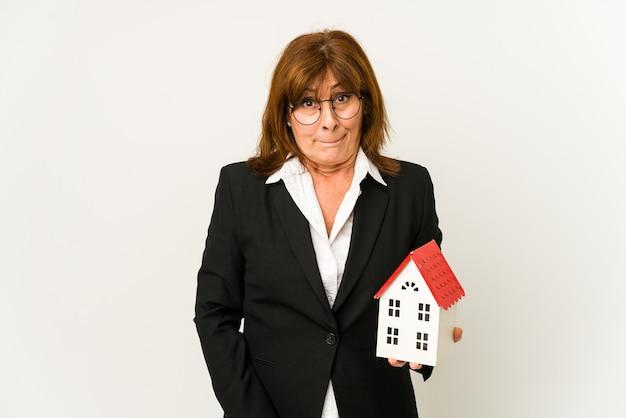 Agent immobilier d'âge moyen tenant un modèle de maison isolé confus, se sent douteux et incertain.