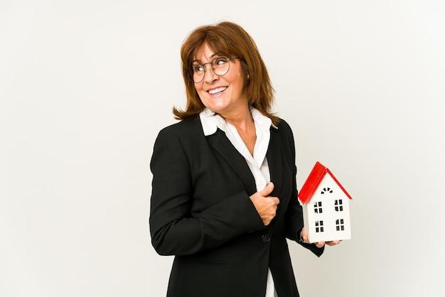 Agent immobilier d'âge moyen tenant un modèle de maison isolé regarde de côté souriant, gai et agréable.
