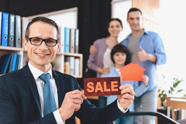 Agent immobilier assis au bureau et présentant le signe de la vente.