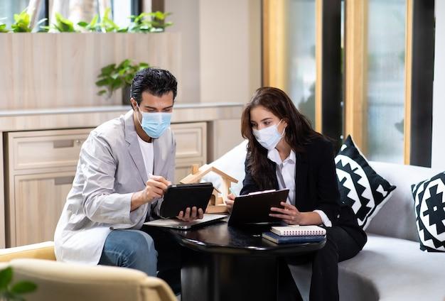Agent immobilier de belle femme offrant et montrant une présentation en ligne sur un ordinateur portable au bureau à un bel homme. personnes portant un masque facial protecteur contre le virus corona.