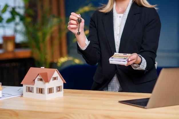 Agent Immobilier Avec Clé De Maison Et Argent Entre Les Mains. Photo Premium