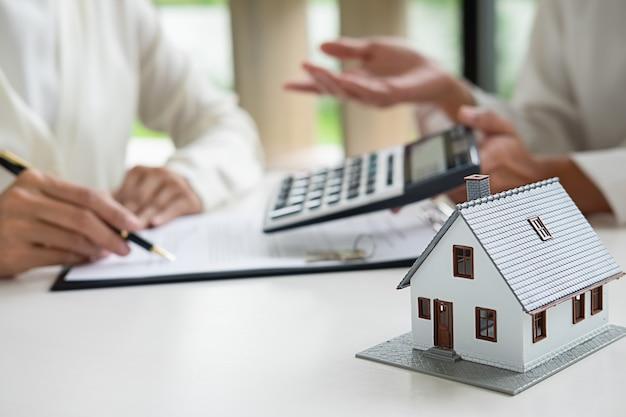 Agent immobilier et client signant un contrat d'achat de maison, d'assurance ou de prêt immobilier.