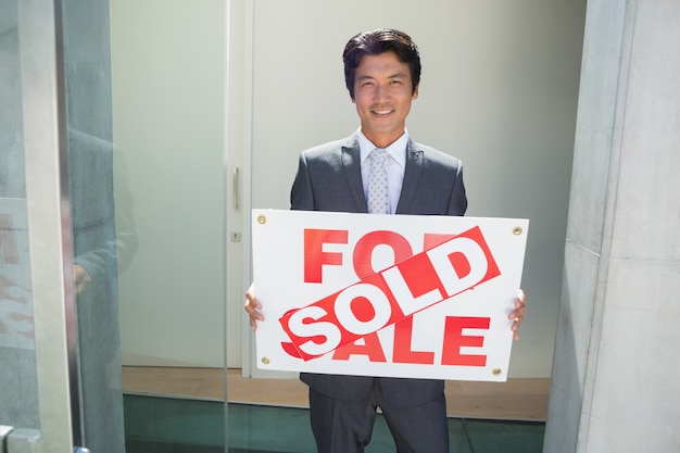 Agent immobilier confiant debout à la porte d'entrée montrant le signe vendu