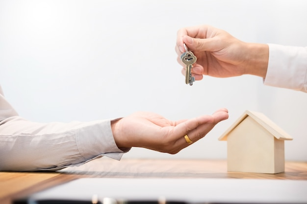 Agent immobilier en costume assis dans un bureau de bureau remettre des clés de maison avec client après signature de contrat