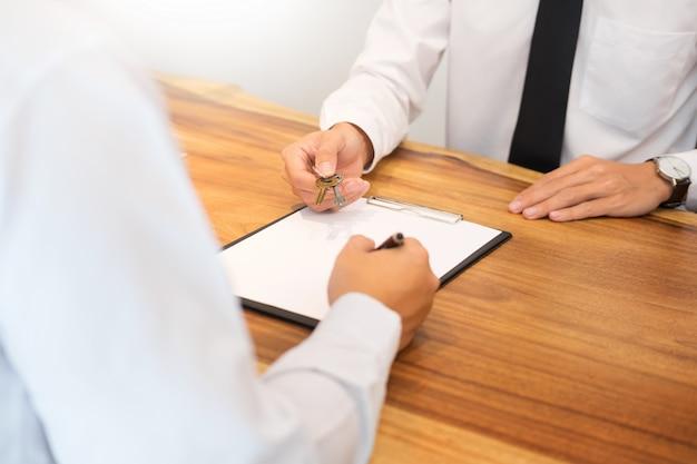 Agent immobilier en costume assis dans un bureau de remise des clés de la maison