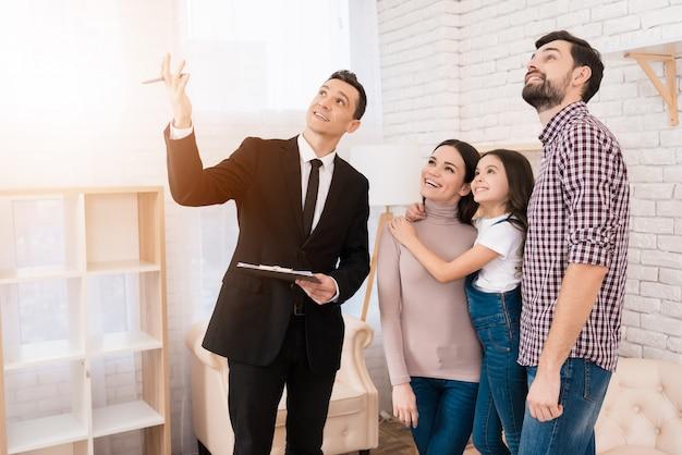L'agent immobilier en costume montre la maison familiale qu'ils ont achetée.