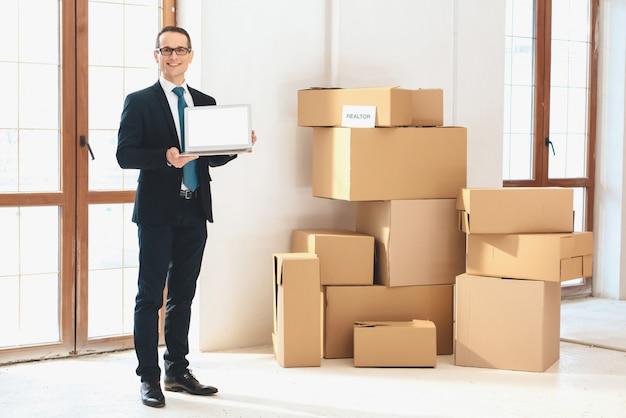 Agent immobilier en costume tenant un ordinateur portable avec écran blanc.