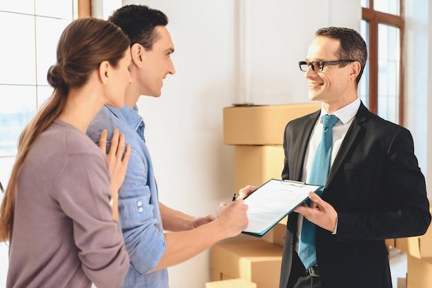 Agent immobilier demande à un homme de signer sur la tablette.
