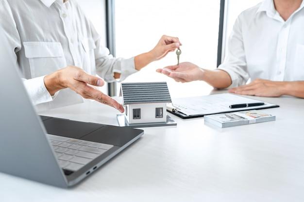 Agent immobilier donnant la clé au client après la signature du contrat de location