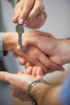 Agent immobilier donnant la clé de la maison au client tout en se serrant la main