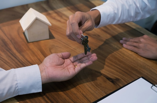 Agent immobilier donnant des clés au client après la signature du contrat.