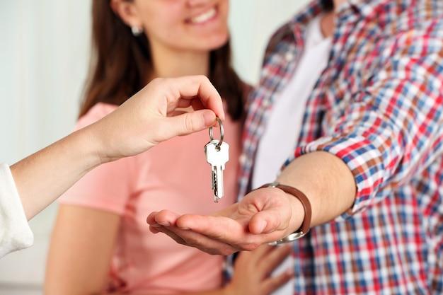 Agent immobilier donnant des clés au jeune couple