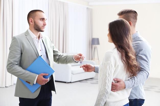 Agent immobilier donnant les clés de couple, sur fond clair