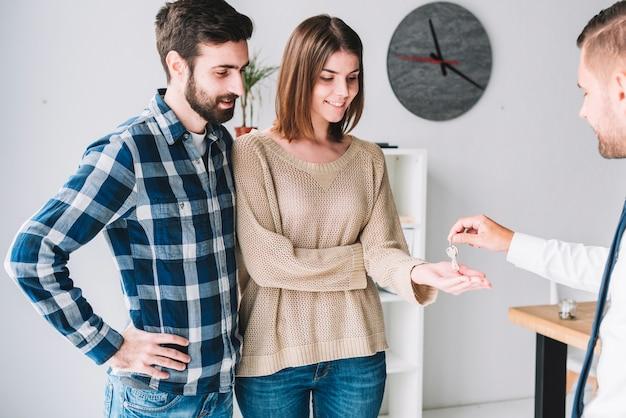 Agent immobilier donnant des clés pour couple