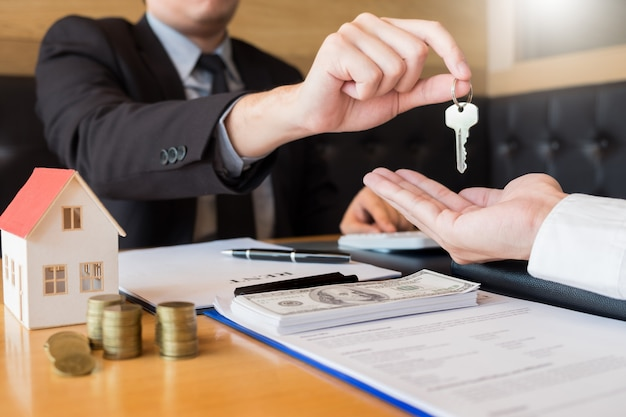 Agent immobilier donnant à la maison les clés de la signature du client
