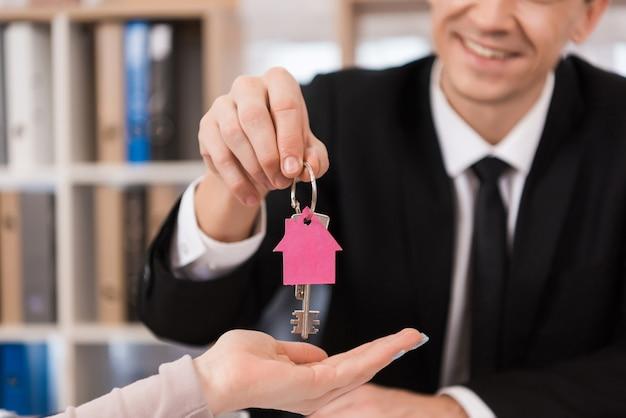 Agent immobilier donne des clés femme avec porte-clés sous forme de maison