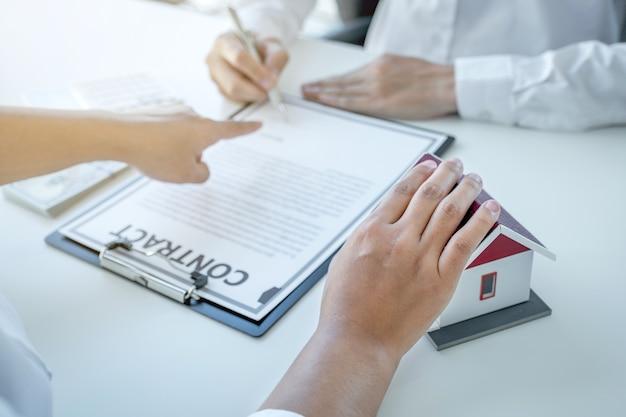 L'agent immobilier explique le contrat commercial, le loyer, l'achat, l'hypothèque, un prêt ou une assurance habitation à l'acheteur féminin.