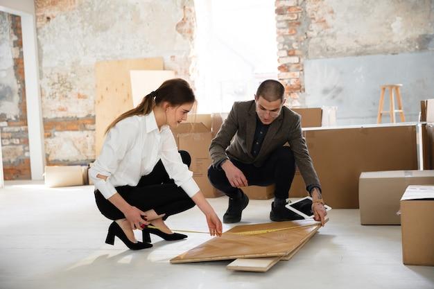 Agent immobilier féminin montrant une nouvelle maison à un jeune homme après une discussion sur les plans de maison déplaçant le nouveau concept de maison