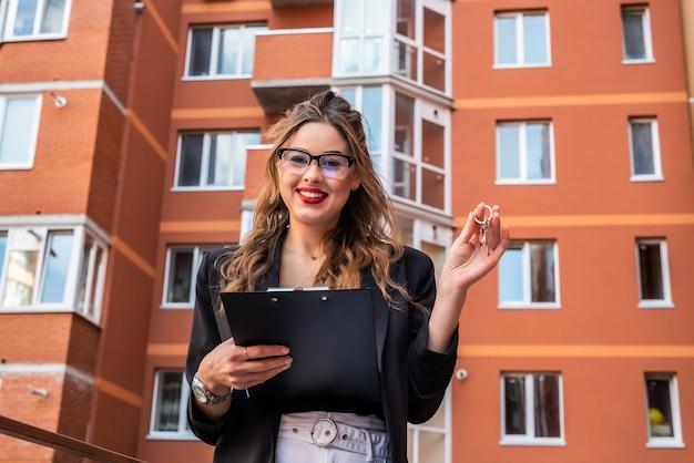 Agent immobilier féminin tenant le trousseau sous la forme d'une petite maison et clés contre maison en arrière-plan