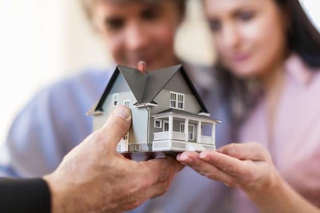 Agent immobilier montrant une maquette de maison à un couple heureux