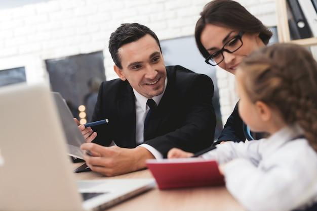 Agent immobilier montrant le plan sur l'ordinateur portable à la mère et l'enfant.