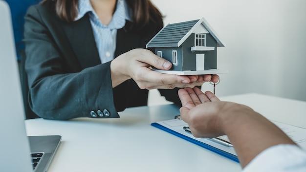 Un agent immobilier offre un modèle de maison à la femme acheteuse.