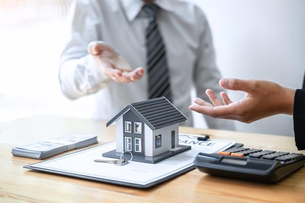 L'agent immobilier présente un prêt immobilier et donne une maison au client après avoir discuté et signé un contrat d'accord avec le formulaire de demande approuvé, l'assurance habitation et le concept d'investissement immobilier.