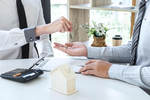 L'agent immobilier présente un prêt immobilier et envoie des clés au client après avoir signé un contrat pour acheter une maison avec un formulaire de demande de propriété approuvé, concept insurance home.