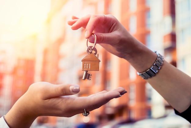 Agent immobilier remettant la clé de la maison pour le nouveau propriétaire à la maison. vendre ou louer une maison