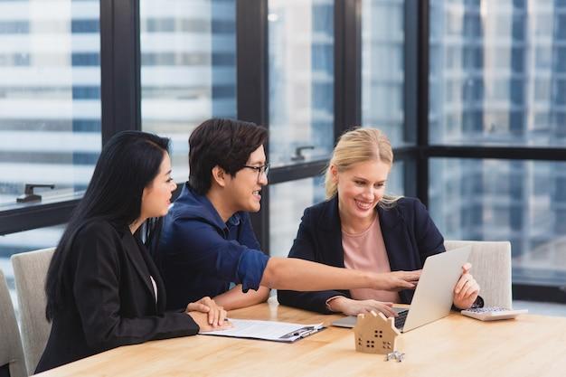 Agent immobilier rencontre un couple asiatique pour offrir l'accession à la propriété, l'assurance-vie et l'investissement dans la maison