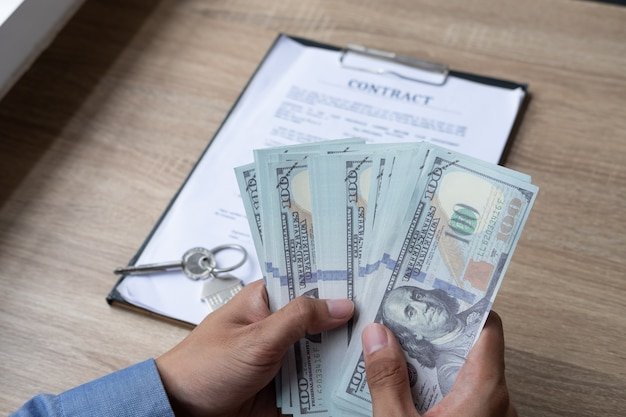 Agent immobilier de sexe masculin comptant l'argent après un contrat avec succès pour l'achat d'une maison.