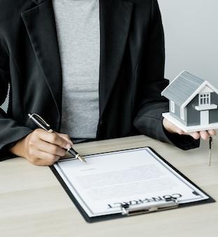 L'agent immobilier signe avec la clé du modèle de maison et explique le contrat commercial ou l'assurance à la femme acheteuse