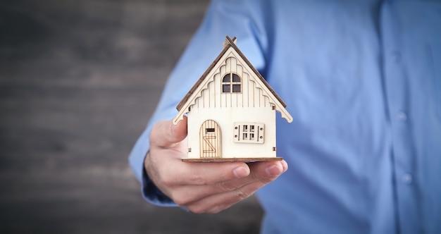 Agent immobilier tenant un modèle de maison en bois.