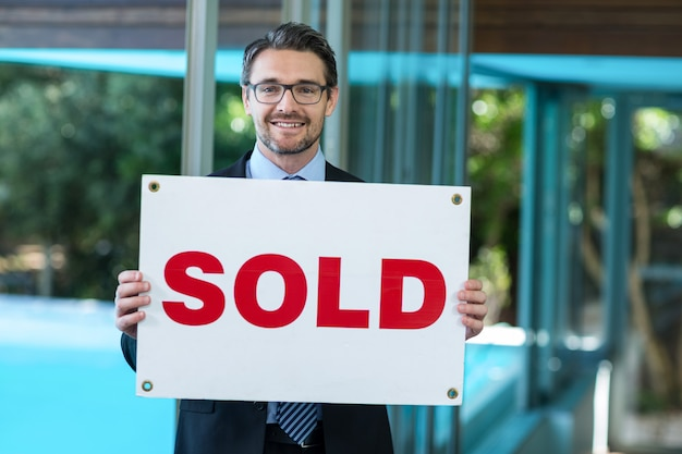 Agent immobilier tenant une pancarte vendue