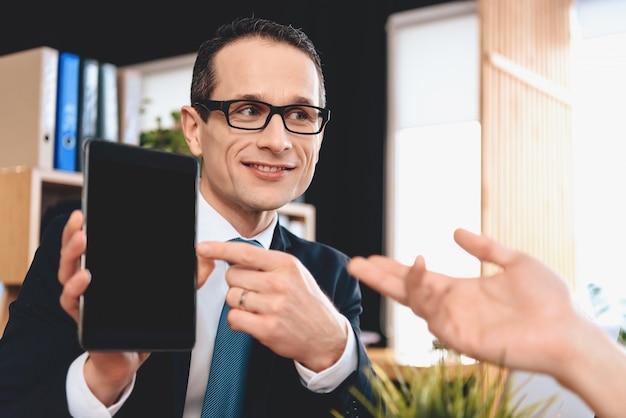 L'agent immobilier tient la tablette, le père la montre du doigt.
