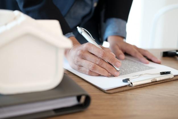 Agent immobilier travaillant avec modèle de maison, prêt hypothécaire et achat de biens immobiliers de location