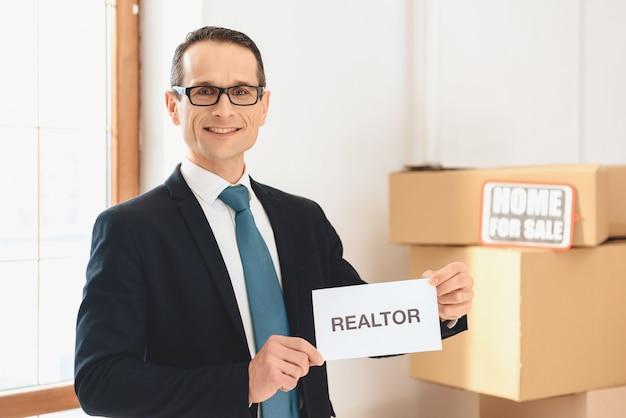 Agent immobilier en verre tenant une pancarte d'agent immobilier.
