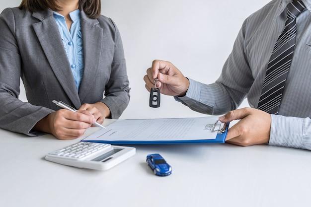 Agent de location de voiture donnant la clé d'une nouvelle voiture à un client