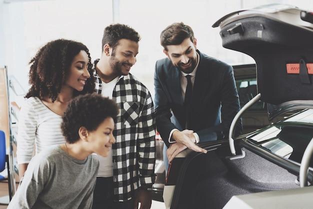 Un agent montre une famille de véhicules inspectant une voiture neuve